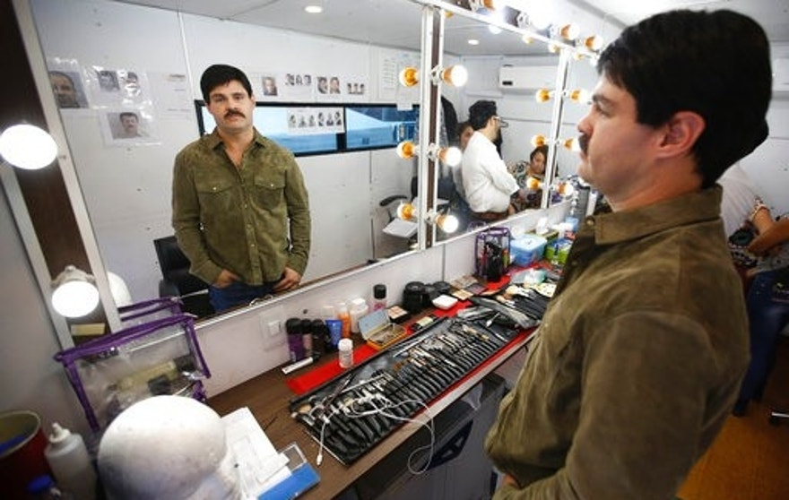 In this March, 21, 2017 photo, Mexican actor Marco de la O looks at his reflection in the dressing room during a pause in the filming of the TV series about the life of Mexico's drug lord Joaquin Guzman, in Tabio, Colombia. De la O, a Mexican stage actor bears an extraordinary resemblance to the drug lord after coming out of a makeup session. (AP Photo/Fernando Vergara)