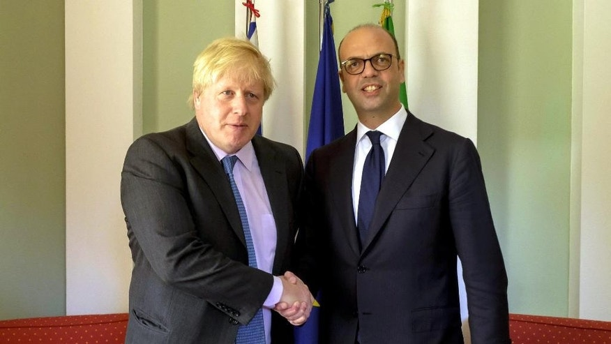 Italian Foreign Minister Angelino Alfano shakes hands with British Secretary of State Boris Johnson, left, on the occasion of a bilateral meeting in Forte di Marmi, near Lucca, Monday, April 10, 2017. (Riccardo Dalle Luche/ANSA via AP)