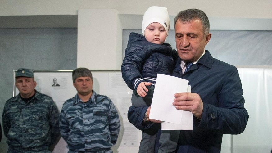 Presidential candidate Anatoly Bibilov with his grandson Ignat casts his ballot during presidential elections in Tskhinvali in Georgia's breakaway province of South Ossetia, Sunday, April 9, 2017. Voters in Georgia's breakaway region of South Ossetia are electing a president and deciding on a referendum on whether to add the word Alania to the region's name, which critics say would be a step toward incorporating South Ossetia into Russia. (AP Photo/Anton Podgaiko)