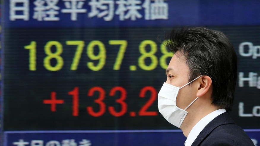 A man walks by an electronic stock board of a securities firm in Tokyo, Monday, April 10, 2017. Asian shares were wavering Monday after attacks by suicide bombers on churches in Egypt added to uncertainties in the Middle East. News that China's top anti-corruption body is investigating the insurance regulator pulled shares in Shanghai and Shenzhen lower. (AP Photo/Koji Sasahara)