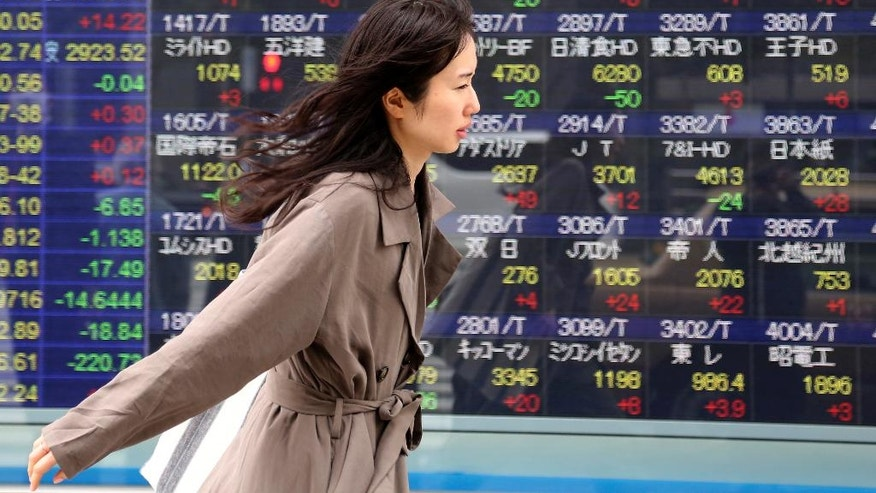 A woman walks by an electronic stock board of a securities firm in Tokyo, Monday, April 10, 2017. Asian shares were wavering Monday after attacks by suicide bombers on churches in Egypt added to uncertainties in the Middle East. News that China's top anti-corruption body is investigating the insurance regulator pulled shares in Shanghai and Shenzhen lower. (AP Photo/Koji Sasahara)
