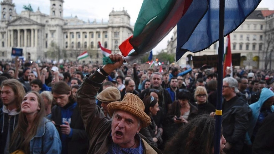 "A demonstrator chants slogans during a protest against the amendment of the higher education law that could force a Budapest university founded by billionaire American philanthropist George Soros to close , in front of the Parliament building in Budapest, Hungary, Sunday, April 9, 2017.  Hungarian President Janos Ader said Monday April 10, 2017, in a statement that he has signed the bill setting new conditions for foreign universities in Hungary which is in line with the Constitution, and called on the government to ""immediately"" begin talks with the affected institutions to secure compliance with the new rules. (Zoltan Balogh/MTI via AP)"