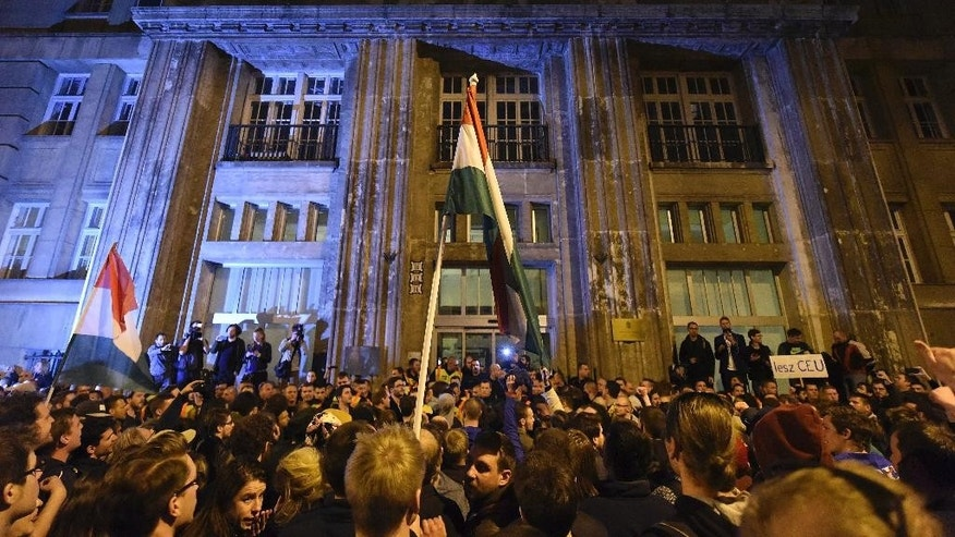 "Demonstrators chant slogans during a protest against the amendment of the higher education law that could force a Budapest university founded by billionaire American philanthropist George Soros to close, in front of the Ministry of Human Resources, in Budapest, Sunday, April 9, 2017.   Hungarian President Janos Ader said Monday April 10, 2017, in a statement that he has signed the bill setting new conditions for foreign universities in Hungary in line with the Constitution, and called on the government to ""immediately"" begin talks with the affected institutions to secure compliance with the new rules.(Zoltan Balogh/MTI via AP)"