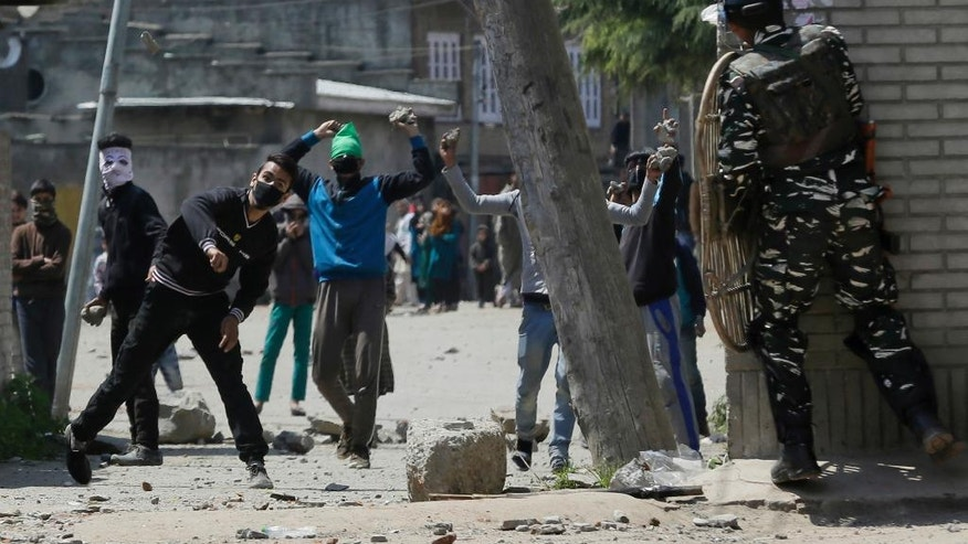 Kashmiri protesters throw stones on Indian security men outside a poling station during a by-election to an Indian Parliament seat in Srinagar, Indian controlled Kashmir, Sunday, April. 9, 2017. (AP Photo/Mukhtar Khan)