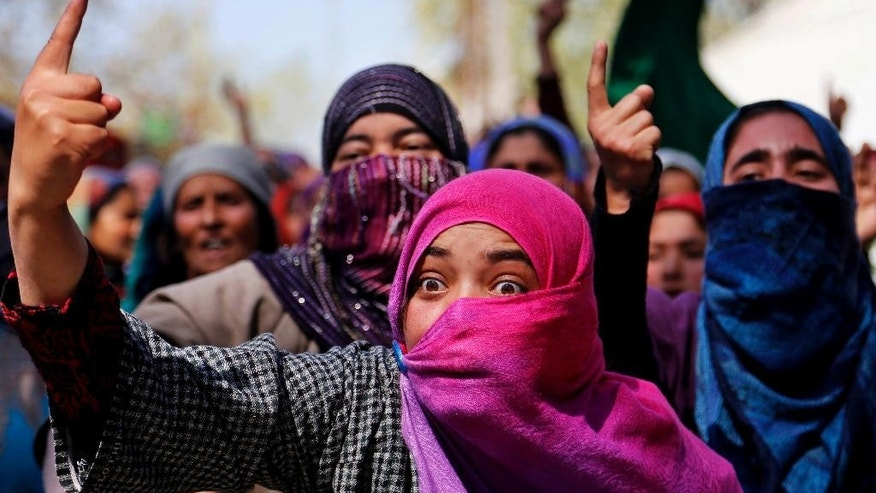 A Kashmiri woman shouts pro freedom slogans during the funeral of Umer Farooq, a Kashmiri civilian who was killed Sunday at Baroosa village 34 Kilometers (21 miles) northeast of Srinagar, Indian controlled Kashmir, Monday, April 10, 2017. Government forces opened fire on Sunday on crowds of people who attacked polling stations during a by-election for a vacant seat in India's Parliament, killing eight people. (AP Photo/Mukhtar Khan)