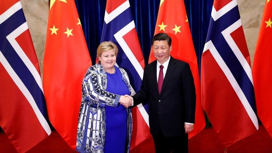 Chinese President Xi Jinping, right, shakes hands with Norwegian Prime Minister Erna Solberg at the Great Hall of People in Beijing, China on Monday April 10, 2017. (Yohei Kanasashi/Pool Photo via AP)