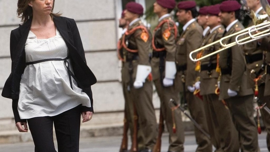 FILE - In this April 14, 2008 file photo, Spain's Defense Minister Carme Chacon reviews troops in Madrid. Chacon, Spain's first female defense minister and a prominent socialist party leader, has died. She was 46. Chacon helped modernize Spain's armed forces when she took the helm of the Ministry of Defense in 2008, in the government of Prime Minister Jose Luis Rodriguez Zapatero. Photos of Chacon reviewing the troops while heavily pregnant became a symbol of a new era in Spanish politics. (AP Photo/Bernat Armangue, File)