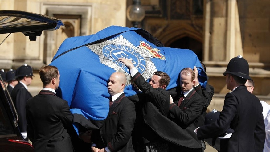 A gust of wind blow as a coffin carrying the late PC Keith Palmer, who was killed in the London attack on March 22, is carried into the Houses of Parliament to rest overnight in the Chapel of St Mary Undercroft in London, Sunday, April 9, 2017. Palmer's funeral is due to take place at Southwark Cathedral in London on Monday. (AP Photo/Matt Dunham)