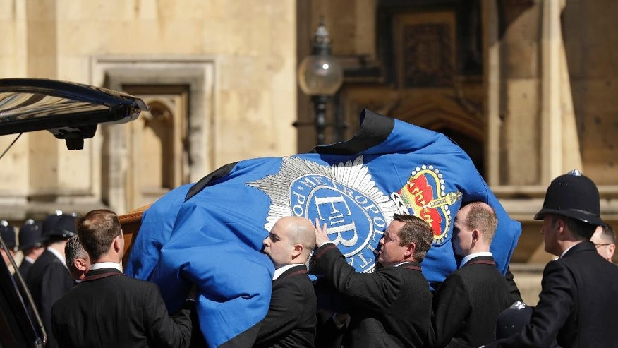 A gust of wind billows the police flag as pallbearers carrying the coffin of late police constable Keith Palmer, who was killed in the London attack on March 22, is carried into the Houses of Parliament to rest overnight in the Chapel of St Mary Undercroft,  in London, Sunday, April 9, 2017. Palmer's funeral is due to take place at Southwark Cathedral in London on Monday. (AP Photo/Matt Dunham)
