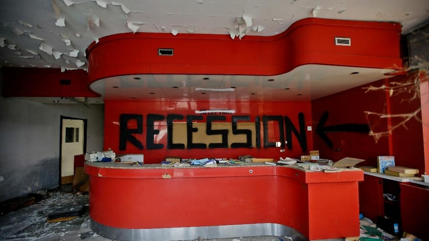 In this photo taken on Thursday, Nov. 3, 2016, the word 'recession' was written on the desk of the reception at the abandoned Hotel Americ in Carpiano, near Milan. Lombardy is Italy's most productive region with an annual GDP of 337 billion euros, making it Europe's second most productive region. And yet the landscape is dotted with ghosts of industries past. (AP Photo/Luca Bruno)