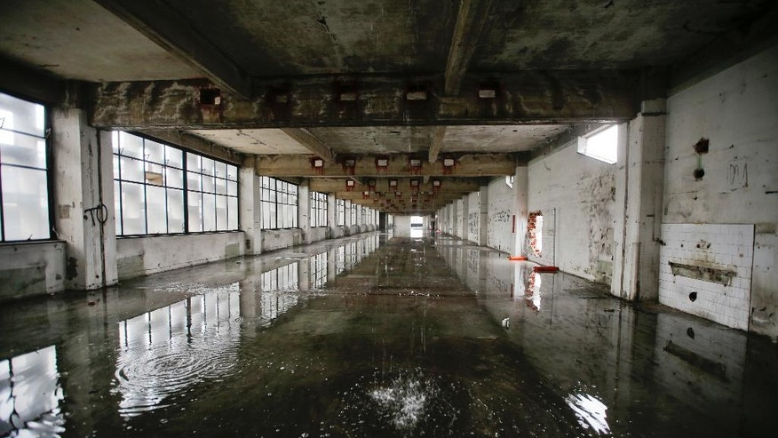 In this photo taken on Friday, Feb. 3, 2017, water comes from the roof inside the abandoned Alfa Romeo car factory, in Arese, near Milan, Italy, Friday, Feb. 3, 2017. Lombardy is Italy's most productive region with an annual GDP of 337 billion euros, making it Europe's second most productive region. And yet the landscape is dotted with ghosts of industries past. (AP Photo/Luca Bruno)