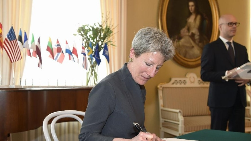 "Foreign Service Officer Donna Welton from the US, signs the Memorandum of Understanding in Helsinki, Finland, Tuesday, April 11, 2017. A group of European Union and NATO nations have agreed to establish a European ""hybrid threat"" center in Finland to combat unconventional methods of warfare such as disinformation and fake news. (Markku Ulander/Lehtikuva via AP)"