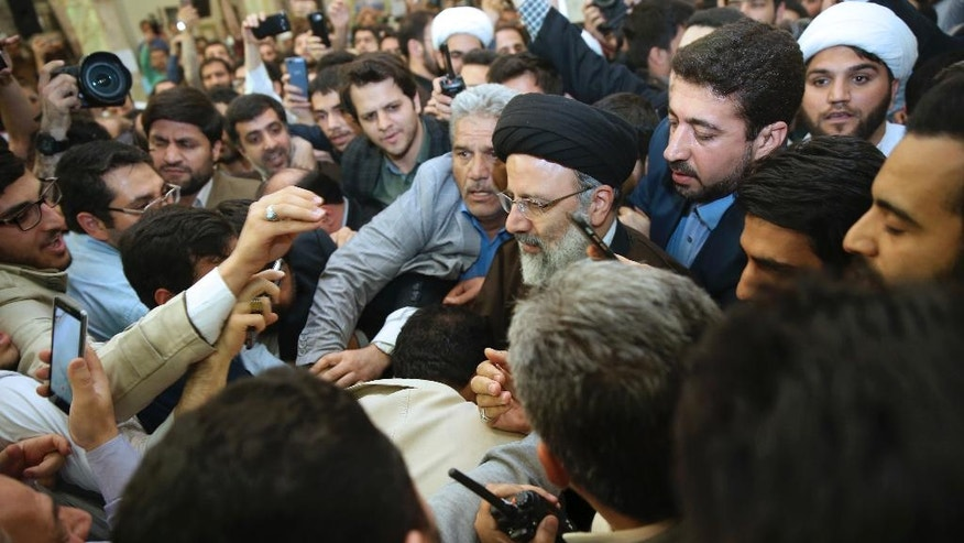 Iranian presidential hopeful Ebrahim Raisi, center, arrives at Houri mosque to deliver a speech in southern Tehran, Iran, Monday, April 10, 2017. Raisi, a hard-line cleric and close ally of Iran's supreme leader, has announced he will run in the May presidential election. Iranian hardliners had hope Raisi would challenge incumbent President Hassan Rouhani, who is eligible to run for a second term. (AP Photo/Vahid Salemi)