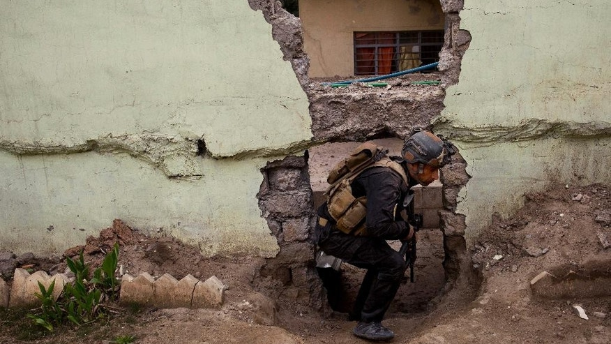 An Iraqi special forces soldier moves through a hole in a wall during heavy fighting in the Yarmouk district of western Mosul, Iraq, Tuesday, April 11, 2017. (AP Photo/Maya Alleruzzo)
