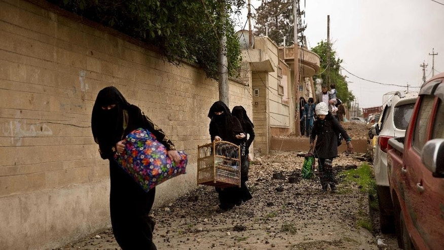 Iraqi women flee heavy fighting in the Yarmouk district of western Mosul, Iraq, Tuesday, April 11, 2017. (AP Photo/Maya Alleruzzo)
