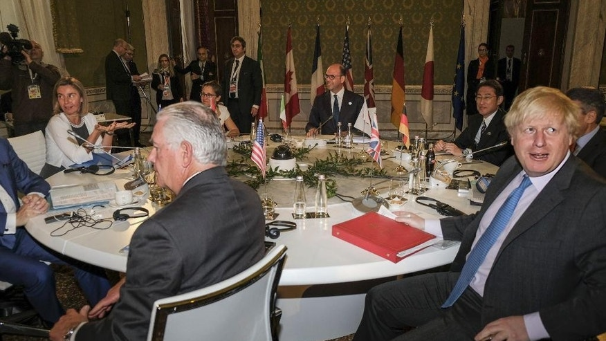 US Secretary of State Rex Tillerson, left, and British Secretary of State for Foreign and Commonwealth Affairs Boris Johnson sit at the table during a meeting of foreign ministers of the G7 in Lucca, Italy, Tuesday, April 11, 2017. Foreign ministers from the Group of Seven industrialized nations are expected to call for a new international push to end the war in Syria as they end a meeting in Italy Tuesday.  (Riccardo Dalle Luche/ANSA via AP)