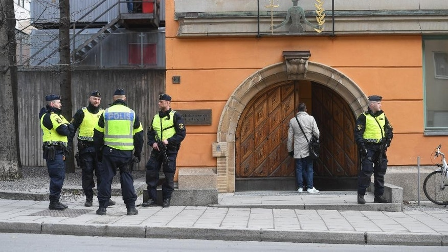 Police with automatic weapons guardthe entrance to Stockholm District Court in Sweden, Tuesday April 11, 2017 for the appearance of Uzbek national Rakhmat Akilov, the accused in Friday's truck crash. Akilov, who is accused of crashing a truck into pedestrians in Stockholm pleaded guilty to terrorist crimes on Tuesday. (Fredrik Sandberg/TT via AP)