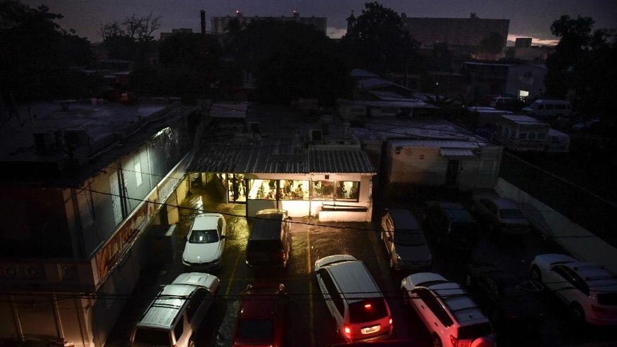 FILE - In this Sept. 22, 2016, file photo, motorists illuminate a storefront with their headlights as they drive in to buy bread after a massive blackout, in San Juan, Puerto Rico. An increase in power outages in 2017, is taking its toll on Puerto Rico as the U.S. territory's heavily indebted public power company struggles to modernize its crumbling infrastructure amid a deep economic crisis. (AP Photo/Carlos Giusti, File)