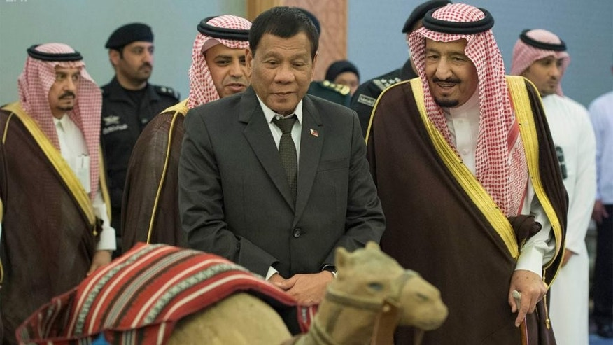 In this photo released by Saudi Press Agency, Saudi King Salman, right, and Philippine President Rodrigo Duterte look at a model of a camel, in Riyadh, Saudi Arabia, Tuesday April 11, 2017. (Saudi Press Agency via AP)