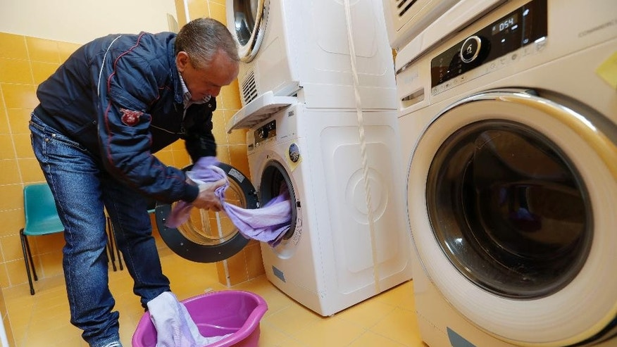 Ciro Guardaccione, a homeless person who is a regular of the Sant'Egidio Community Centre, removes clothes from a washing machine in a laundry opened in this catholic community in Rome, Tuesday, April 11, 2017. Pope Francis has opened a new laundromat for the homeless to wash, dry and iron their clothing and blankets.  The laundromat, not far from the Vatican, has six washing machines, six dryers and several ironing boards and irons. (AP Photo/Alessandra Tarantino)