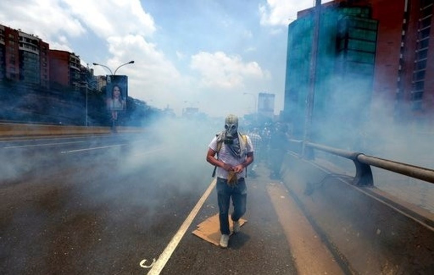 A demonstrator walks in the middle of a cloud of tear gas fired by the Bolivarian National Guard during a protest in Caracas, Venezuela, Monday, April 10, 2017. Thousands of people in Venezuela's capital are protesting against the government of President Nicolas Maduro, demanding new elections and vowing to stay in the streets during the usually quiet Easter Week.(AP Photo/Fernando Llano)