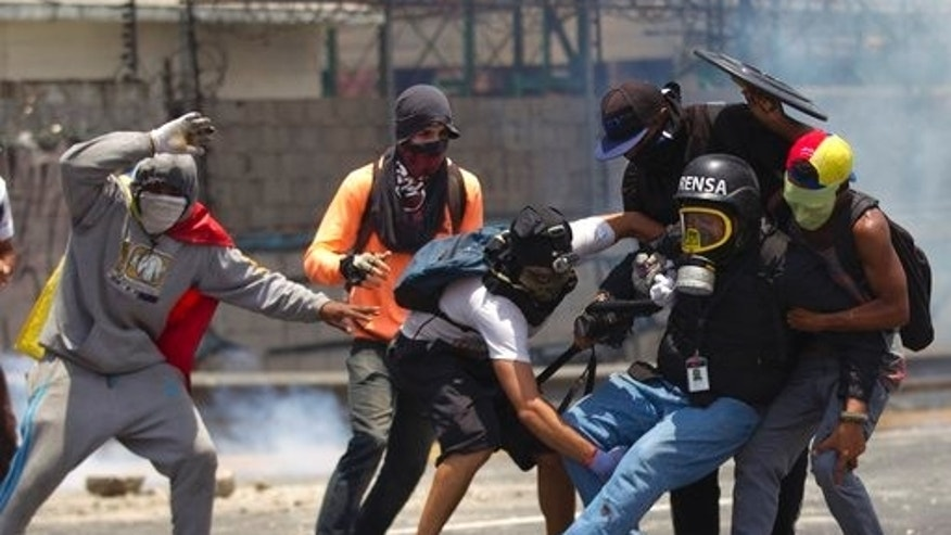 Demonstrators help a journalist who was injured in a leg while covering clashes between demonstrators and the Bolivarian National Guard during a protest in Caracas, Venezuela, Monday, April 10, 2017.