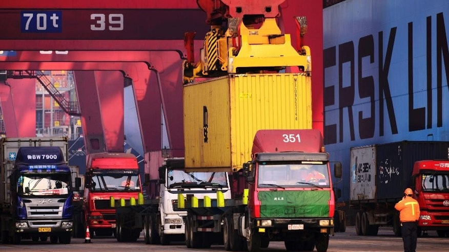 FILE - In this Dec. 8, 2016 file photo, trucks line up at a container port in Qingdao in east China's Shandong province. China's export growth accelerated in March in a positive sign for global demand while import growth cooled, according to customs data Thursday, April 13, 2017. (Chinatopix via AP, File)