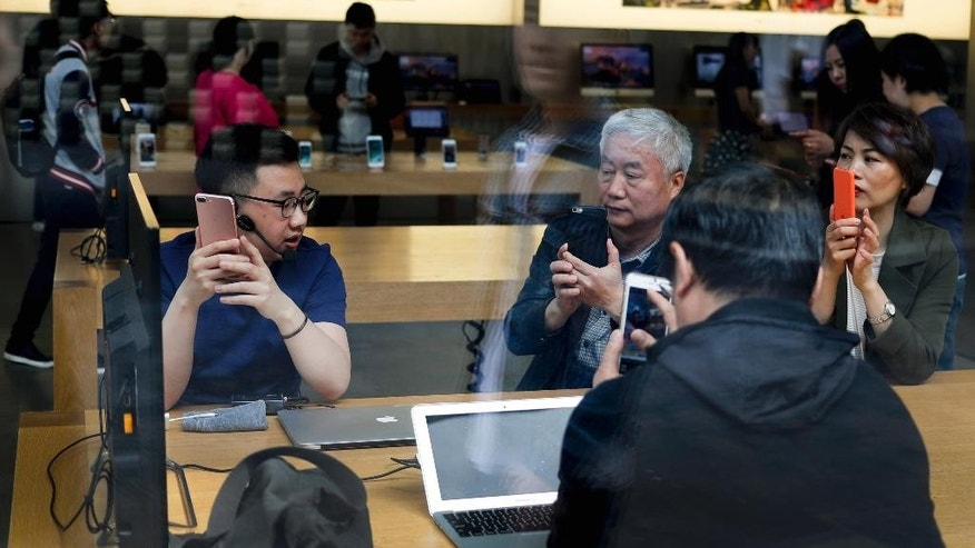 An Apple employee, left, teaches customers how to operate iPhone at its retail store in Beijing, Thursday, April 13, 2017. China's export growth accelerated in March in a positive sign for global demand, though import growth cooled. (AP Photo/Andy Wong)