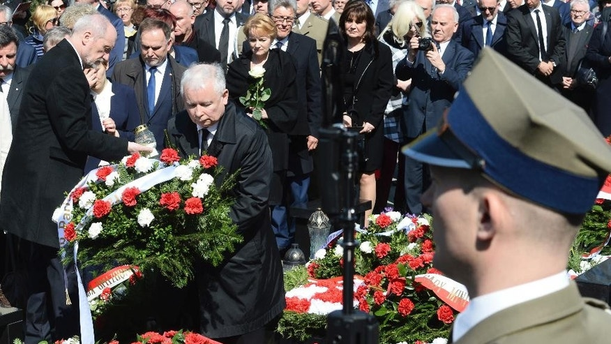 The ruling party Law and Justice leader and twin brother of the former Polish President Lech Kaczynski, Jaroslaw Kaczynski, second left, lays a wreath, as Defense Minister Antoni Macierewicz, left, holds a candle, during a ceremony at the Powazki cemetery to mark the seventh anniversary of the crash of the Polish government plane in Smolensk, Russia, that killed 96 people on board including Lech Kaczynski, in Warsaw, Poland, Monday, April 10, 2017. (AP Photo/Alik Keplicz)