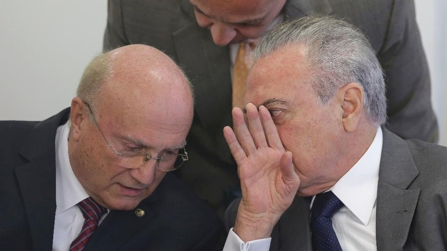 Brazil's President Michel Temer, right, speaks with his Justice Minister Osmar Serraglio, right, during a ceremony at the Planalto presidential palace, in Brasilia, Brazil, Wednesday, April 12, 2017. Brazil's Supreme Court announced corruption investigations into eight ministers and dozens more top politicians in a sweeping decision that affects almost one third of embattled President Michel Temer's Cabinet and many of his top allies. (AP Photo/Eraldo Peres)