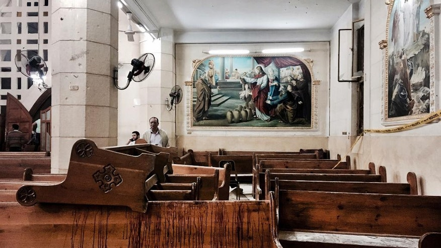 FILE -- In this Sunday, April 9, 2017 file photo, blood stains pews inside the St. George Church after a suicide bombing, in Tanta, Egypt. The Palm Sunday deadly bombings of two churches left Egyptian President Abdel-Fattah el-Sissi grappling with the question of how to defeat a tenacious insurgency by Islamic State group militants. His predicament comes at a time when he's also tackling the problem of repairing a broken economy, carrying out tough reforms that have won praise from economists but have dealt a devastating blow to most Egyptians. (AP Photo/Nariman El-Mofty, File)