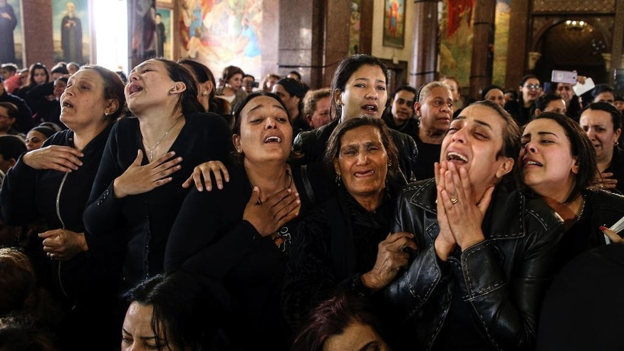 FILE -- In this Monday, April 10, 2017 file photo, women cry during the funeral for those killed in a Palm Sunday church attack, in Alexandria Egypt. The deadly bombings of two churches left Egyptian President Abdel-Fattah el-Sissi grappling with the question of how to defeat a tenacious insurgency by Islamic State group militants. His predicament comes at a time when he's also tackling the problem of repairing a broken economy, carrying out tough reforms that have won praise from economists but have dealt a devastating blow to most Egyptians. (AP Photo/Samer Abdallah, File)