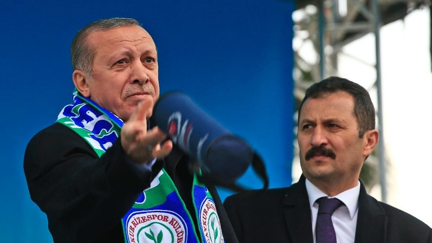 In this photo taken on Monday April 3, 2017, Turkey's President Recep Tayyip Erdogan, left, throws gifts to supporters under the watchful eye of his closest body-guard, right, following his speech at a rally in his hometown Black Sea city of Rize, Turkey. Neatly-trimmed mustaches, similar to that worn by Turkish President Recep Tayyip Erdogan, have become increasingly popular among government ministers from his Islamic-rooted Justice and Development Party, or AKP, ahead of a crucial referendum Sunday, April 16 on expanding the president's powers. Some analysts say that's no fluke in a country where facial hair has a history of political significance, and where ministers' loyalty to Erdogan is being closely scrutinized following a failed coup attempt last year. (AP Photo/Lefteris Pitarakis)