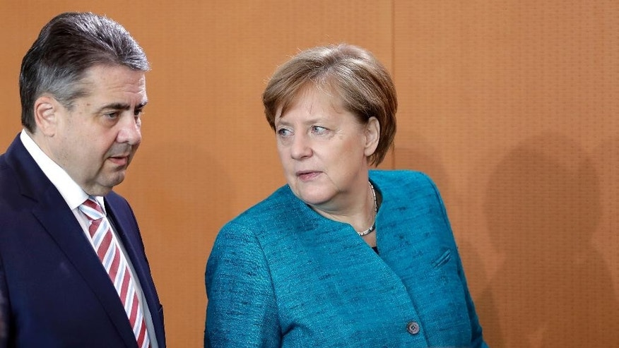 German Chancellor Angela Merkel, right, and German Foreign Minister Sigmar Gabriel, left, arrive for the weekly cabinet meeting at the Chancellery in Berlin, Germany, Wednesday, April 12, 2017. (AP Photo/Michael Sohn)