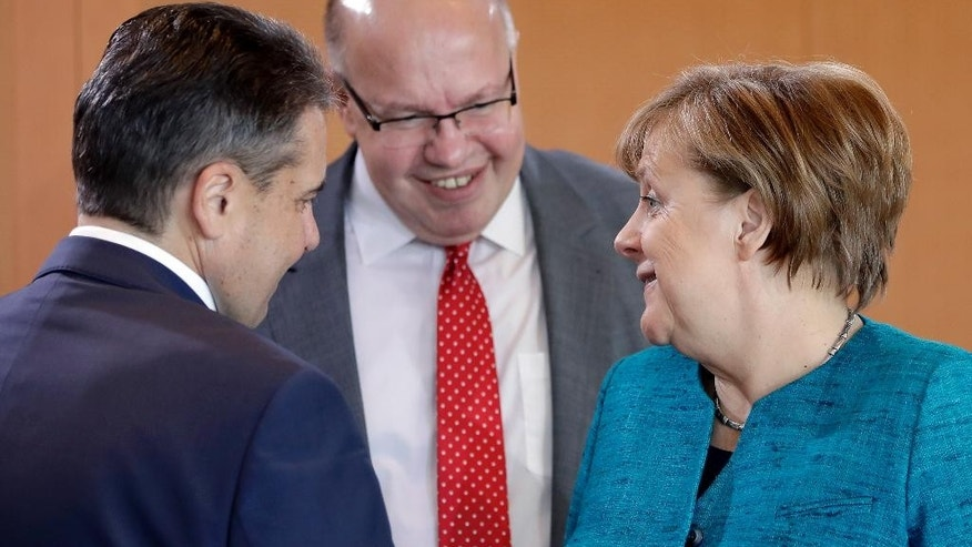 From left, German Foreign Minister Sigmar Gabriel, Peter Altmaier, Head of the Federal Chancellery and Federal Minister for Special Tasks and German Chancellor Angela Merkel talk as they arrive for the weekly cabinet meeting at the Chancellery in Berlin, Germany, Wednesday, April 12, 2017. (AP Photo/Michael Sohn)