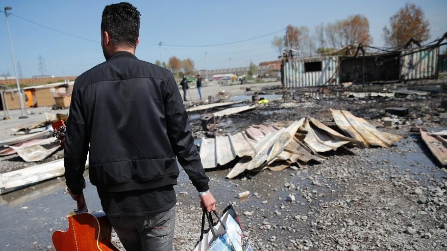 Ismael, a Kurd migrant, carries a guitar he salvaged from the burned remains of a migrant camp in the Dunkirk suburb of Grande-Synthe, northern France, Tuesday, April 11, 2017. Several hundred migrants have disappeared after they were evacuated from a camp in northern France that was ravaged by a shocking fire that left 10 injured, according to authorities and aid workers trying to ensure alternative shelter and calm tensions. (AP Photo/Christophe Ena)