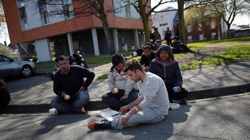Migrants eat as they gather in front of a gymnasium where they take shelter in the Dunkirk suburb of Grande-Synthe, northern France, Tuesday, April 11, 2017. Several hundred migrants have disappeared after they were evacuated from a camp in northern France that was ravaged by a shocking fire that left 10 injured, according to authorities and aid workers trying to ensure alternative shelter and calm tensions. (AP Photo/Christophe Ena)
