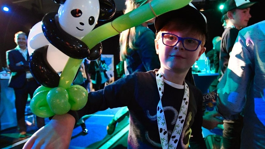 A young boy carries a balloon modelled panda as he waits for the arrival of giant pandas female Wu Wen and male Xing Ya at Schiphol Airport in the Netherlands from China on Wednesday, April 12, 2017. The pair of three-and-half year old giant pandas are being taken from Schiphol Airport to the Ouwehands Zoo in the central Dutch town of Rhenen where they will settle into a purpose-built enclosure for a 15-year stay as part of a nature conservation project. (AP Photo/Patrick Post)