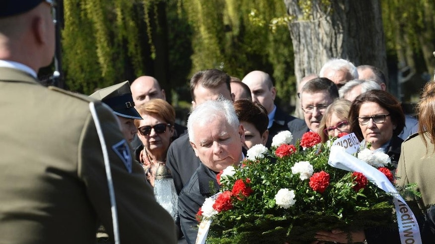 The ruling party Law and Justice leader and twin brother of the former Polish President Lech Kaczynski, Jaroslaw Kaczynski, center, lays a wreath during a ceremony at the Powazki cemetery to mark the seventh anniversary of the crash of the Polish government plane in Smolensk, Russia, that killed 96 people on board including Lech Kaczynski, in Warsaw, Poland, Monday, April 10, 2017. (AP Photo/Alik Keplicz)