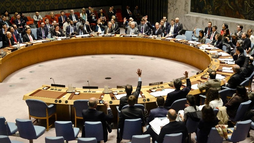 CORRECTS DATE TO APRIL 12 - United Nations Security Council members show hands for a vote on a resolution condemning Syria's use of chemical weapons at U.N. headquarters on Wednesday, April 12, 2017. (AP Photo/Bebeto Matthews)