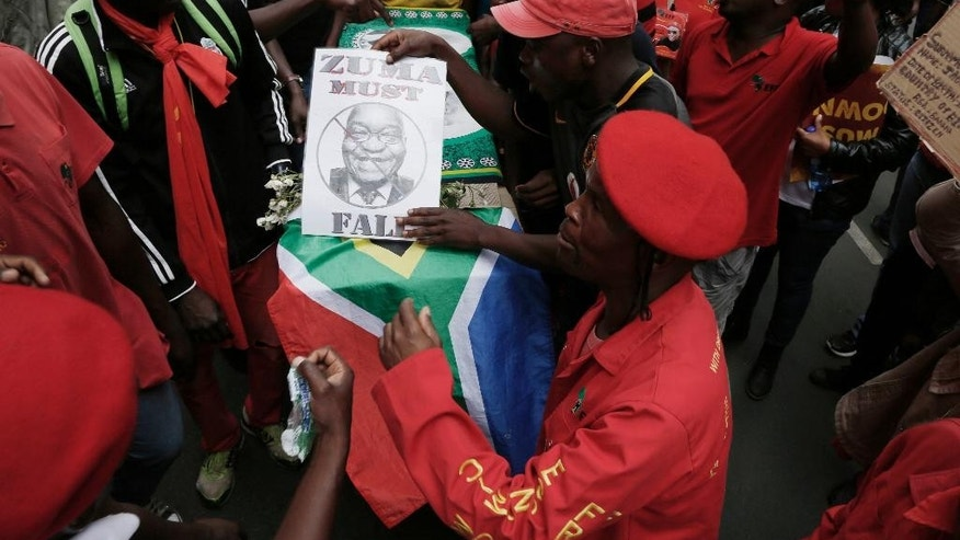 Members of the Economic Freedom Fighters carry a mock coffin in a march to the Government Union Buildings in Pretoria, South Africa Wednesday, April 12, 2017. South Africa's opposition groups marked the 75th birthday of President Jacob Zuma with a protest against him, pushing for his resignation because of scandals and his dismissal of a widely respected finance minister. (AP Photo/Denis Farrell)