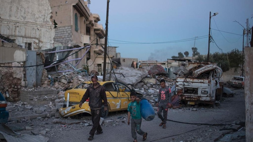 In this April 5, 2017 photo, Firas Mohammed al-Jibouri, left, walks with his son and brother on their destroyed street in Mosul, Iraq. The destruction on a single street in Mosul underscores the cost of breaking the Islamic State group's hold in the Iraqi city. All but two houses have been reduced by airstrikes to piles of concrete, brick and metal. With few supplies, residents are left stunned and traumatized, recounting stories of relatives and neighbors crushed in their homes. (AP Photo/Felipe Dana)