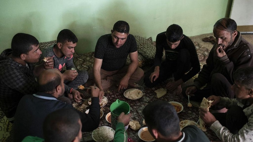 In this April 5, 2017 photo, Firas Mohammed al-Jibouri, top right, eats lunch with family members inside his house in Mosul, Iraq. The destruction on a single street in Mosul underscores the cost of breaking the Islamic State group's hold in the Iraqi city. All but two houses have been reduced by airstrikes to piles of concrete, brick and metal. With few supplies, residents are left stunned and traumatized, recounting stories of relatives and neighbors crushed in their homes. (AP Photo/Felipe Dana)
