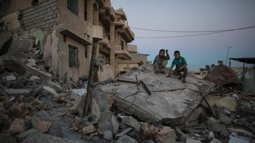 FILE -- In this April 5, 2017 file photo, two boys pose for a photo while sitting atop a destroyed house in a neighborhood recently retaken by Iraqi security forces from Islamic State militants, in west Mosul, Iraq. The destruction on a single street in Mosul underscores the cost of breaking the IS group's hold in the Iraqi city. All but two houses have been reduced by airstrikes to piles of concrete, brick and metal. With few supplies, residents are left stunned and traumatized, recounting stories of relatives and neighbors crushed in their homes. (AP Photo/Felipe Dana, File)