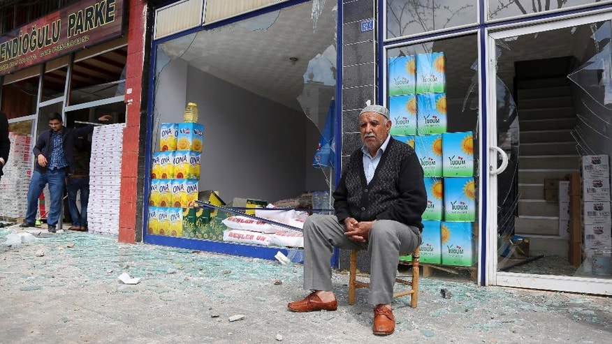 A shop owner sits near the site after an explosion in Diyarbakir, Turkey, Tuesday, April 11, 2017. An explosion inside a workshop where a police armored vehicle was being repaired killed one man and injured a number of other people, Turkish police said Tuesday. The blast in the mainly Kurdish city of Diyarbakir caused part of the workshop — an annex to the city's main police headquarters — to collapse.(AP Photo)