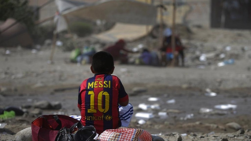 FILE - In this March 24, 2017 file photo, a boy, wearing a jersey of FC Barcelona's Lionel Messi, eats his lunch amidst the devastation caused by the recent floods in Carapongo, Peru. UNICEF announced on Wednesday, April 12, that close to 15 thousand babies and infants are at risk of malnutrition, after the damage caused by the floods. (AP Photo/Martin Mejia, File)