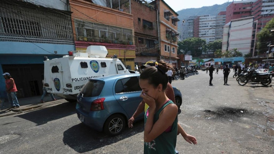 A resident covers her month from tear gas fired by Bolivarian National Police outside of a grocery and liquor store, to disperse looters during a protest in Caracas, Venezuela, Wednesday, April 12, 2017. Residents blocked some roads with debris and derelict furniture, burned garbage and banged pans to protest against Venezuela's President Nicolas Maduro. (AP Photo/Fernando Llano)