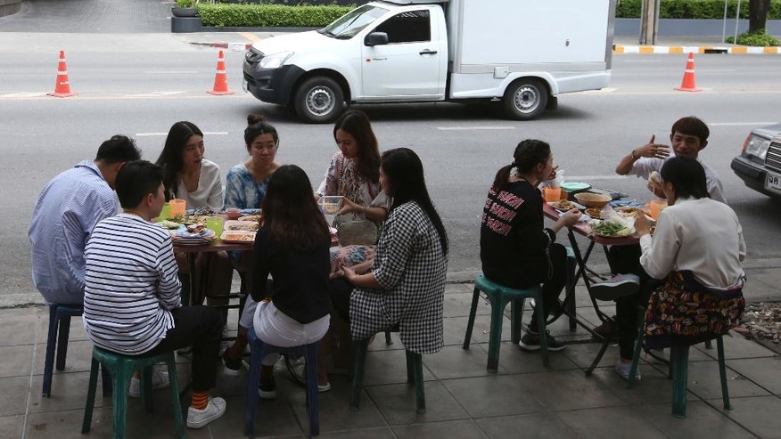 In this April 7, 2017 photo, people have their lunch at a street food shop on Thonglor road in Bangkok, Thailand. Officials see street food as an illegal nuisance and have warned hawkers in Thonglor to clear out by April 17. Efforts by authorities in military-ruled Thailand to impose order on the chaotic capital city have a fresh target: cheap and tasty pad thai. The latest crackdown by Bangkok city officials is going after the vendors whose carts selling everything from Thailand's signature noodles to spicy tom yum goong soup have become institutions on the capital's hot and humid sidewalks. (AP Photo/Sakchai Lalit)