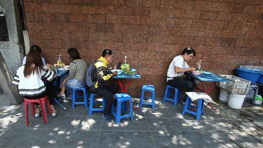 In this April 7, 2017 photo, people eat noodles at a street food stall during their lunch on Thonglor road in Bangkok, Thailand. Officials see street food as an illegal nuisance and have warned hawkers in Thonglor to clear out by April 17. Efforts by authorities in military-ruled Thailand to impose order on the chaotic capital city have a fresh target: cheap and tasty pad thai. The latest crackdown by Bangkok city officials is going after the vendors whose carts selling everything from Thailand's signature noodles to spicy tom yum goong soup have become institutions on the capital's hot and humid sidewalks. (AP Photo/Sakchai Lalit)