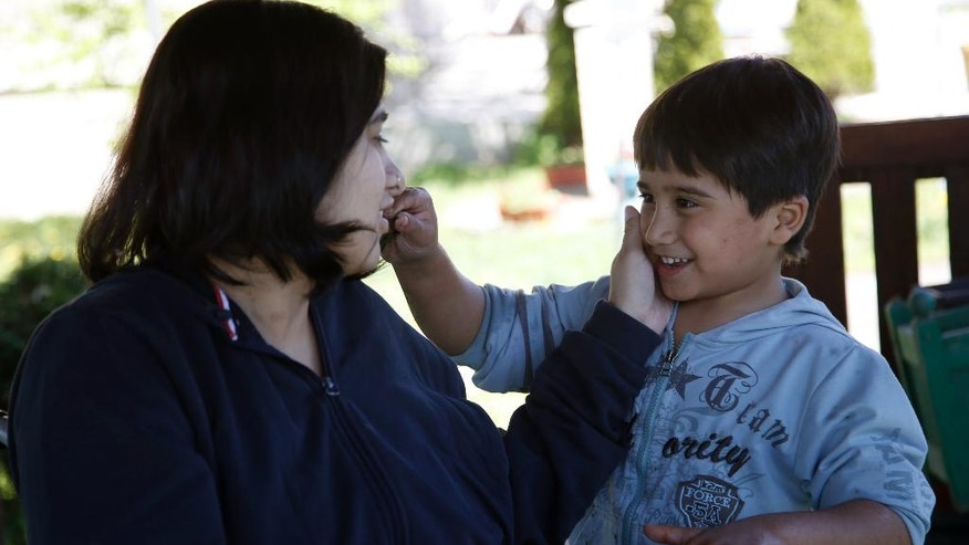 Fatima Bakhshi, a migrant from Afghanistan, left, talking to her five-year-old son Ahmed, in a small care home in the village of Doljevac, in southern Serbia, Monday, April 10, 2017. Bakhshi's tragedy illustrates the dangers facing migrants _ particularly women _ who are relying on people smugglers to take them over lands and borders in hopes of rebuilding their lives in the West. (AP Photo/Darko Vojinovic)